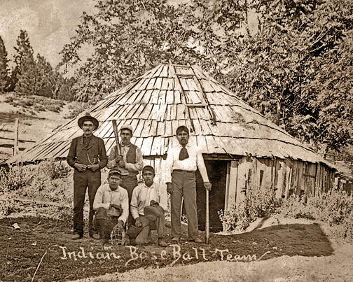 Indian Baseball Team standing in front of the last Roundhouse to stand on the Rancheria.